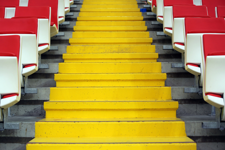 tribune: Yellow stairs and rows of seats at the tribune of modern stadium Stock Photo