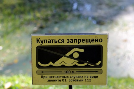 prohibited: Swimming is prohibited. Yellow sign in Russian Stock Photo