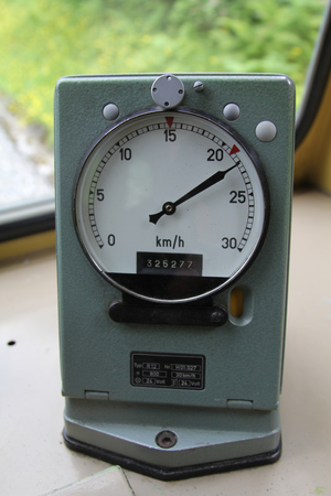the outdated: Outdated round railroad speedometer in the cabin of trains driver