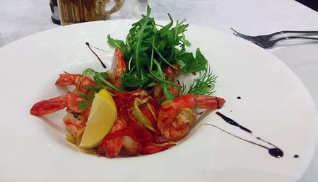 ruccola: Salad with fried shrimp, ruccola and lemon served on a white porcelain plate