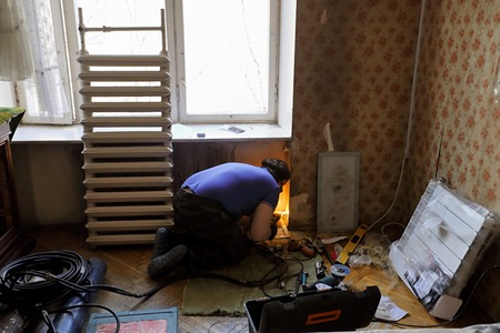 replaces: Worker replaces domestic radiator in the living room