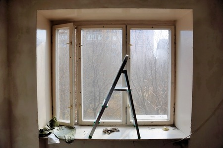 stepladder: Small aluminum stepladder standing at old window in the room