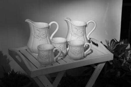 milk jugs: Two white porcelain milk jugs and three cups on a serving table