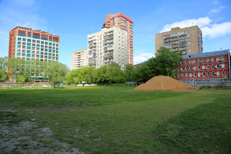 housing lot: Big pile of sand on a wasteland near the apartment buildings