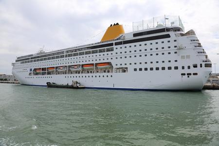 multistory: Multistory white passenger ocean ship parked in the dock Stock Photo