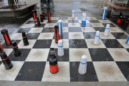 black giant: Giant black and white chess figures on the pavement in the rain