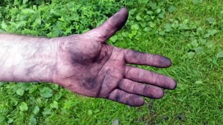 Adult mens hand smeared with charcoal, dirt and dust
