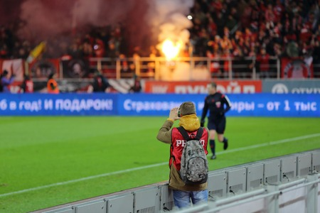 ultras: MOSCOW, RUSSIA - SEPTEMBER 11, 2014: Press photographer at the tribune with the fans in the football stadium Otkrytie Arena Editorial