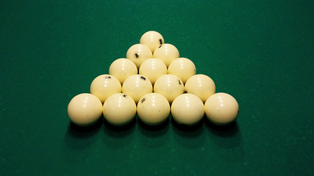 Ivory billiard ball on the green cloth of the table to play