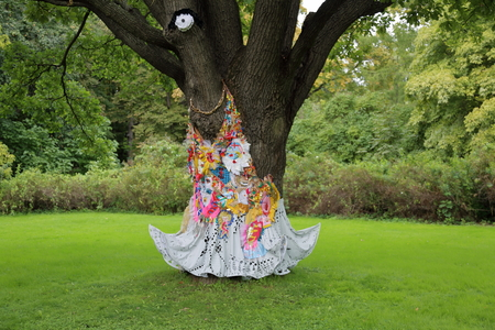 Bicentennial oak tree in a city park is decorated in white robes Stock Photo