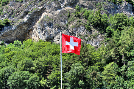 anton: Swiss national flag at the background of the picturesque local landscape Stock Photo