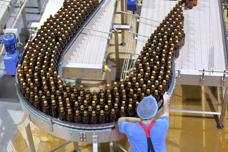 bottling: Worker wearing special protective clothing carries out quality control of beer in the factory for bottling Stock Photo