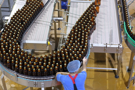 Worker wearing special protective clothing carries out quality control of beer in the factory for bottling Stock Photo