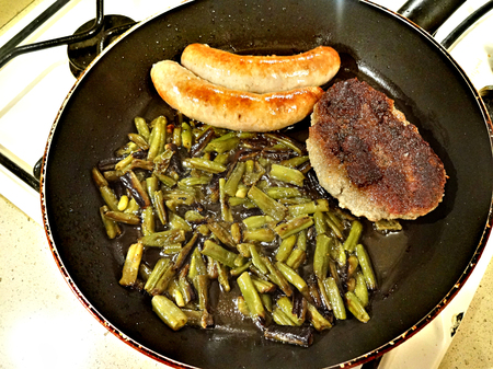 Green beans, sausages and schnitzel fried in a pan Stock Photo