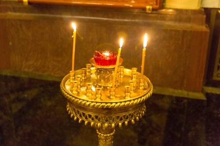temple burn: Wax candles on a floor candlestick in the Christian temple Stock Photo