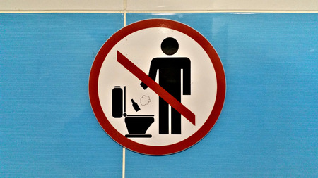 Sign prohibits throwing bottles and foreign objects down the pan in a public toilet