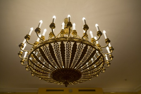 Old forged chandelier with multiple bright lamps Stock Photo