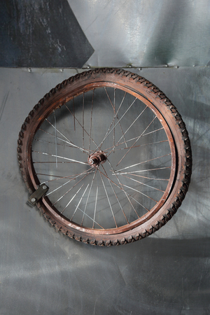 spokes: Rusty old bicycle wheel with broken spokes in a cluttered garage