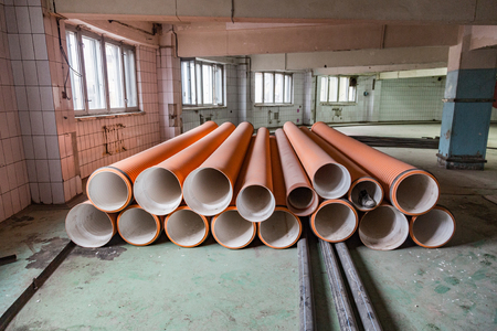 Long industrial pipes of different diameters lie in the shop of the production plant