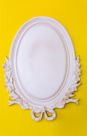 stucco: Frame oval shape of white plaster on a bright yellow background
