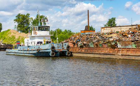 A small old ship sails along the river in a sunny day
