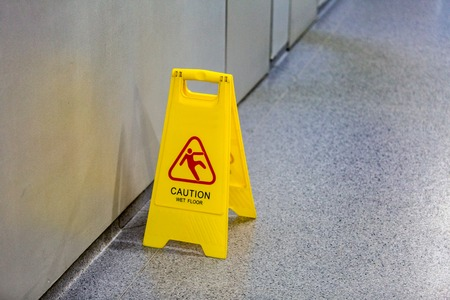 Yellow plastic warning wet floor sign standing on the ground Reklamní fotografie - 88494875