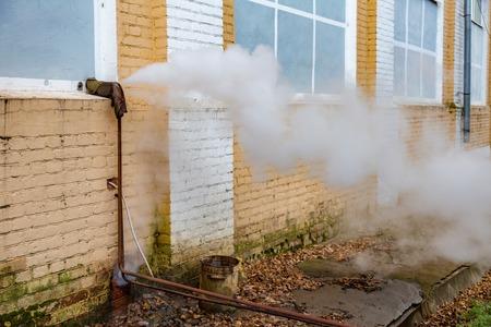 Thick steam broke through a pipe on a brick wall
