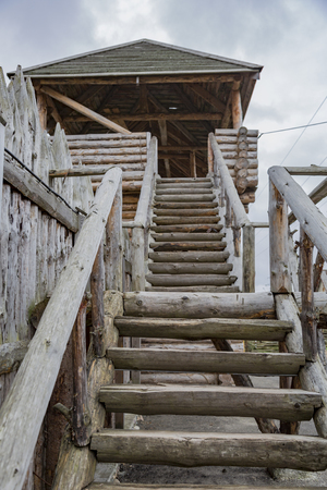 Stairs up from old wooden cracked logs