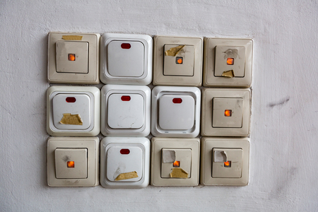 Twelve electric switches in a row on a light plastered wall Standard-Bild