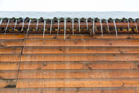 Icicles hanging from the eaves of the wooden building Stock Photo