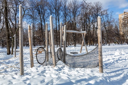 Snow-covered childrens playground in public park in winter