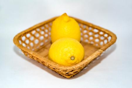 Two yellow lemon in a wicker basket on a white background Reklamní fotografie