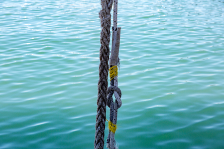 Thick mooring ship rope against the background of sea water