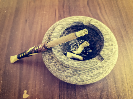 Smoldering cigarillos with a wooden mouthpiece in an ashtray with ash Stock Photo