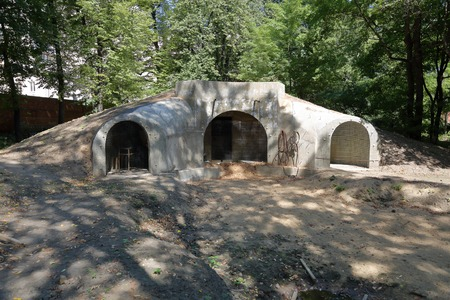 An abandoned bomb shelter with arches and soil embankment