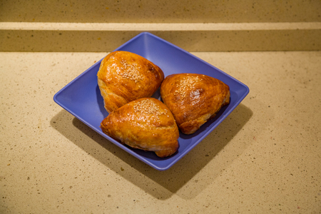 Samsa. Sesame pie with filling on a blue plastic plate. Traditional dish in Central Asia