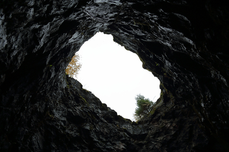 View of the sky and trees from the bottom of a stone mine Stok Fotoğraf