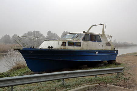 White-blue abandoned rusty boat on the banks of a misty river