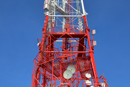 Red and white cell tower on iron pylons against a blue sky 写真素材