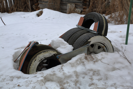 Old used tires piled up in a snowy yard
