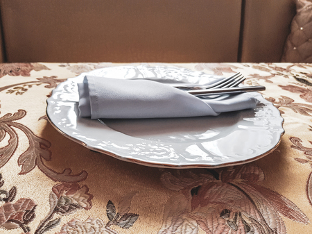 White faience plate and cotton napkin on the dining table