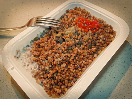 Buckwheat porridge with mushrooms, onions and ketchup in a white disposable plate