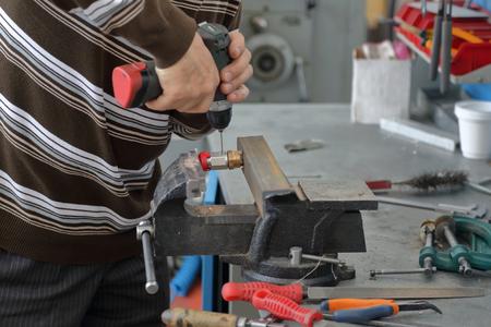 Handyman handles part in cast-iron vice in repair shop