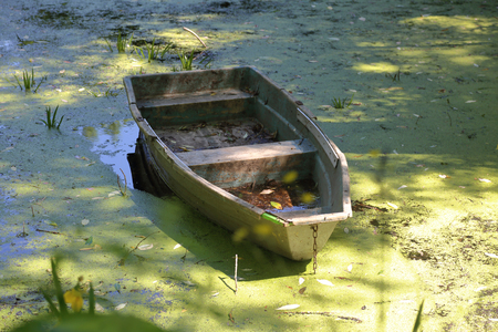 Old abandoned iron boat in a duckweed pond Stockfoto
