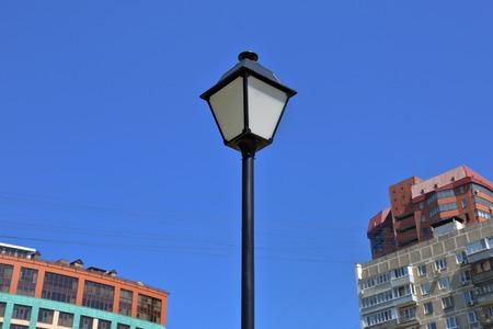 Vintage iron lantern on a city street against the blue sky