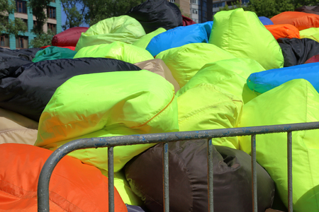 Chaotically heaped soft multi colored armchairs-bags in a city park Stockfoto