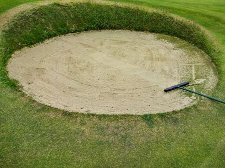 The round playground and rake in the green of the golf course
