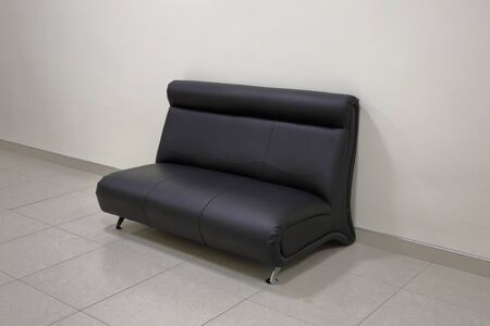 A comfortable sofa made of genuine black leather stands near the wall 写真素材