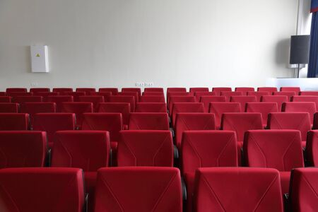 Rows of red seats in an empty room for presentations, press conferences and seminars 写真素材
