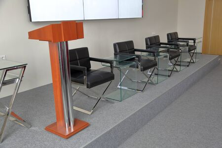 Leather chairs, glass tables and a tribune for speeches on the stage in the hall for presentations 写真素材
